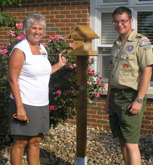 Ruth Southards, Patient Care Coordinator for Hospice, and soon-to-be Eagle Scout Zach Miller pose with one of 18 new bird feeders Zach crafted for St. Anthony's deGreeff Hospice House as his Eagle Scout project.