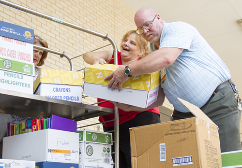 Carol Yeargain and Monroe Diestel, members of the Franciscan Outreach Team at St. Anthony's Medical Center, help load school supplies being donated to the Jefferson County Salvation Army.