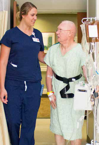 Nurse Assistant Amy Klotz at St. Anthony's Medical Center uses a gait belt to help her patient, Larry Leidner.
