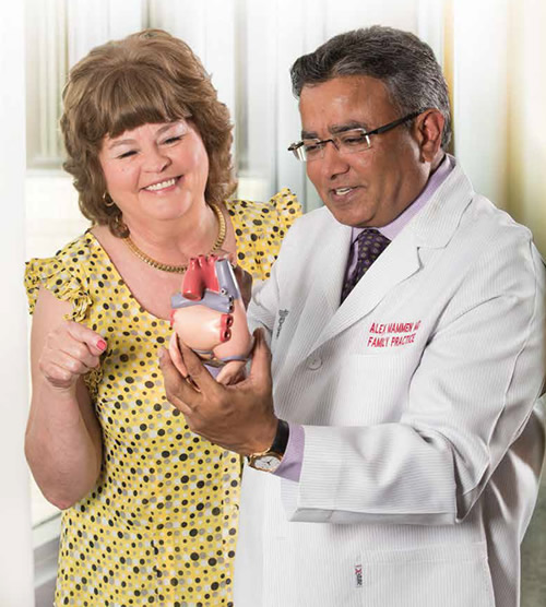 Dr. Mammen discusses the anatomy of a heart with his patient, Phyllis Dees.