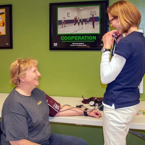 Marty Thurman receives a blood pressure screening from Jane Koslowski at Hancock Place Elementary.