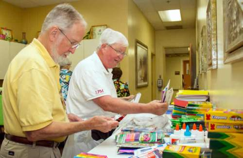 Volunteers and retired teachers John Wich and Larry McCauley sort through school supplies.